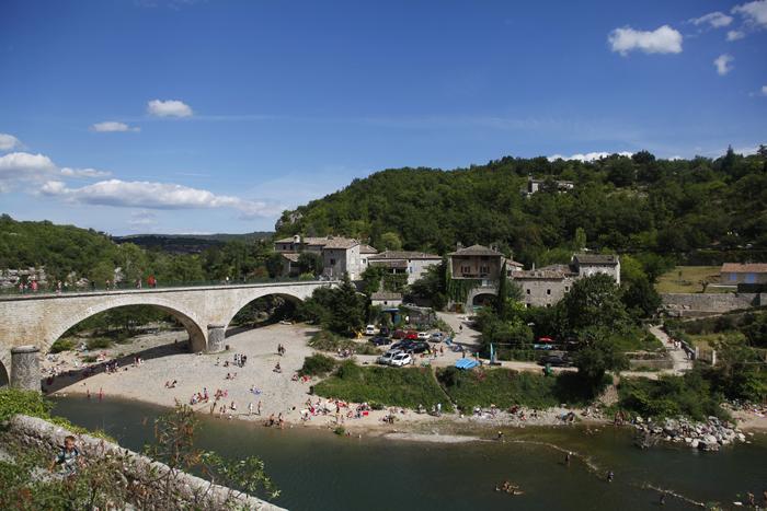 Le grand pont de Balazuc et sa plage jonchée de canoës
