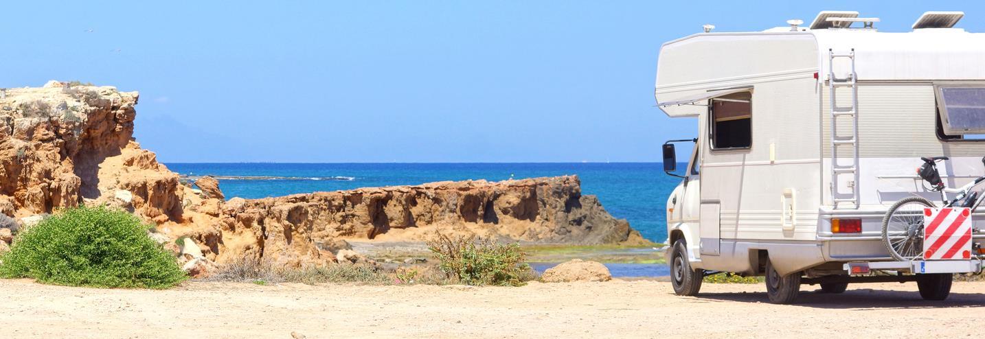Wohnmobil an der Küste mit Blick auf das blaue Meer