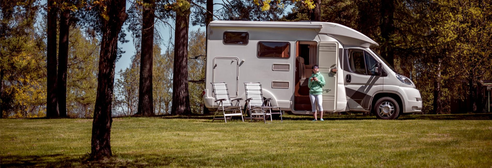 Frau steht mit Kaffeetasse vor ihrem Camperwagen umgeben von Bäumen