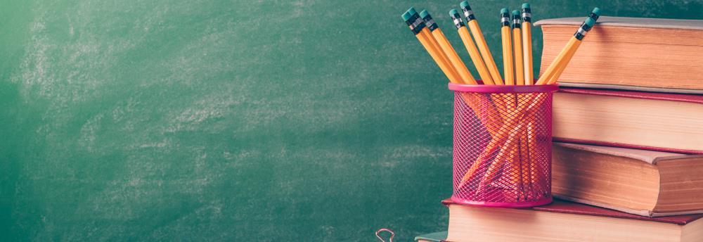Notizzettel, Bleistifte und Bücher, im Hintergrund eine Tafel
