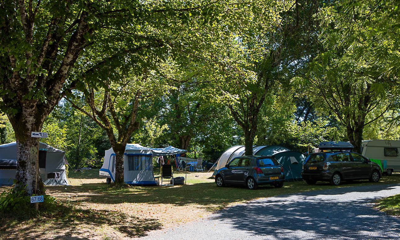 Emplacement camping avec voiture, tente et caravane